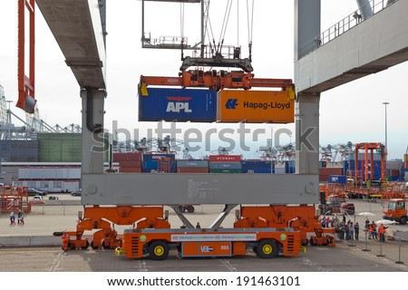 ROTTERDAM - SEP 8: Gantry crane operator moves containers on Sep 8, 2013 in Rotterdam, Netherlands. The port is the Europ's largest and facilitate the needs of a hinterland with 40,000,000 consumers.  - stock photo
