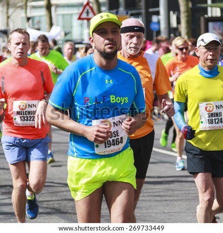 ROTTERDAM, THE NETHERLANDS  APRIL 12, 2015: Colorful runners competing in the 35th NN Rotterdam Marathon held in the city center. The marathon is well known for its fast times. - stock photo
