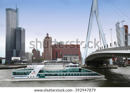 ROTTERDAM, THE NETHERLANDS - 18 AUGUST: View on Erasmus Bridge (Erasmusbrug) and skyline of Rotterdam with a cruise boat, river Maas in Rotterdam, Netherlands on August 18,2015. - stock photo