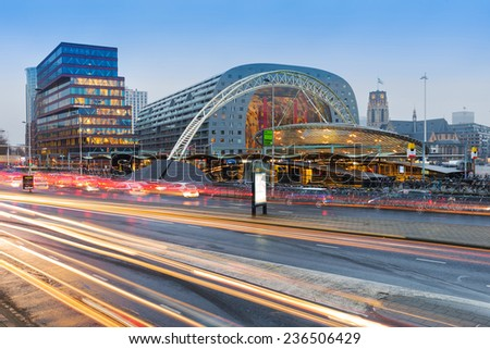 ROTTERDAM, THE NETHERLANDS - DECEMBER 5, 2014: Rotterdam's busy Blaak train station with the new Market Hall behind. - stock photo