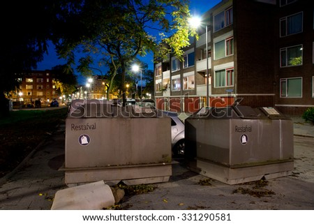 ROTTERDAM, THE NETHERLANDS - OCTOBER 09, 2012: Two metal waste containers by apartment buildings in the night - stock photo
