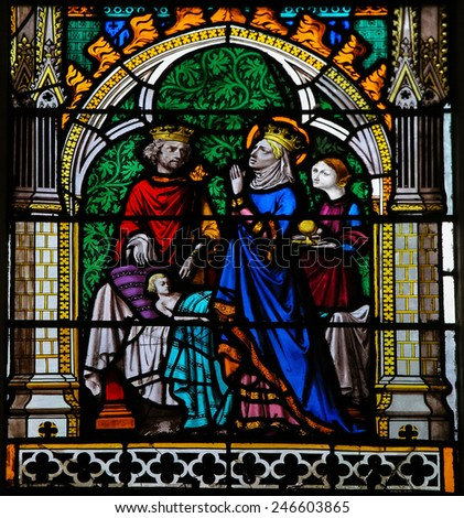 ROUEN, FRANCE - FEBRUARY 10, 2013: Stained glass window depicting a King and Queen praying for their ill son, in the Cathedral of Rouen, France.