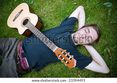 rough country guy laying in the grass with his guitar - stock photo