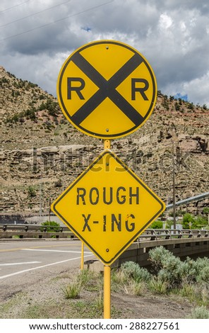 Rough crossing sign attached to a railroad crossing sign to give motorists a warning - stock photo