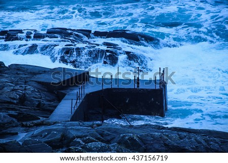 Rough ocean waves against the coastline close to a lighthouse - stock photo