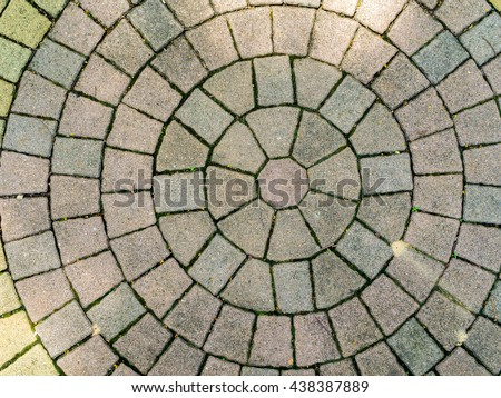 rough old red yellow grey stone paving street is circle round pattern surface top view with sun light