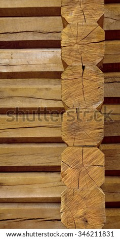 Rough russian chalet room of stacked aged beige hew cracky octagonal balks in traditional slavic style. Closeup view with space for text on crooked brown crack fond. Row of dried cut trunk bars decor - stock photo