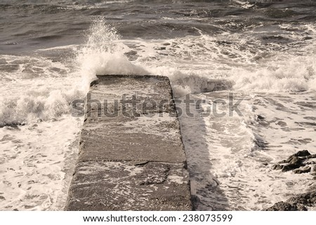 rough sea covering a cement pier. Shot in Alghero, Italy - stock photo