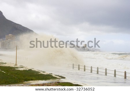 Rough seas crash against the beachfront during a storm. Cape Town, South Africa - stock photo