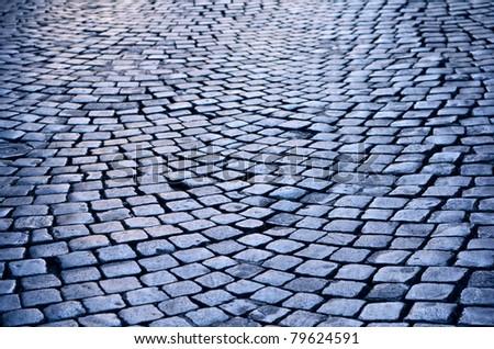 Rough texture of wet cobblestones, old side-street - stock photo