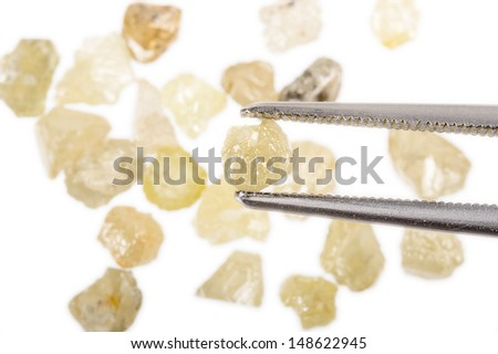 Rough, uncut Diamonds in several colors. One held by tweezers. - stock photo