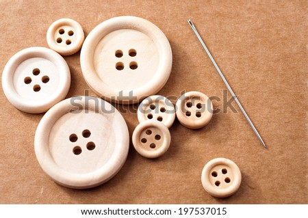 Rough, unpolished, wooden buttons and a needle on a piece of brown carton - stock photo
