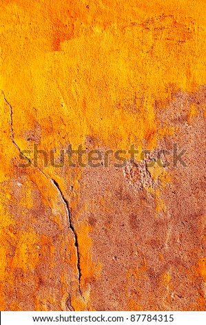 Rough wall with cracks in yellow. - stock photo