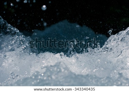 rough water with splashes on a black background - stock photo