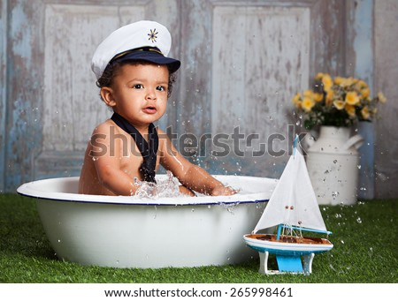 Rough waters!  Adorable toddler sitting in a wash basin full of water, wearing a sailor hat and tie and splashing.   - stock photo