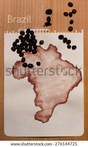 Roughly drawn on the sheet of paper with gouache map of Brazil and coffee beans on it - stock photo