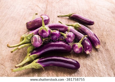 Round and long fresh organic raw purple brinjal or eggplant or aubergine. Healthy and delicious purple eggplants on wood table. (Selective focus). - stock photo