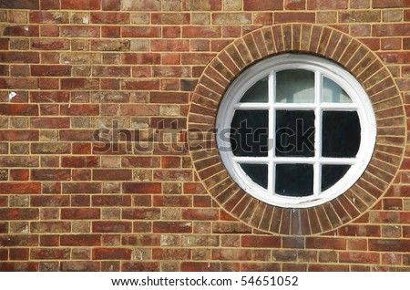 round and vintage wooden window on a brick wall building - stock photo