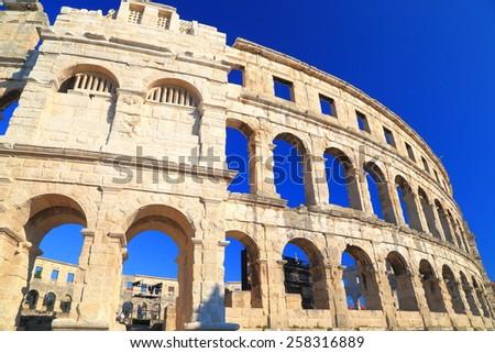 Round arches decorate ancient Roman amphitheater, Pula, Croatia - stock photo