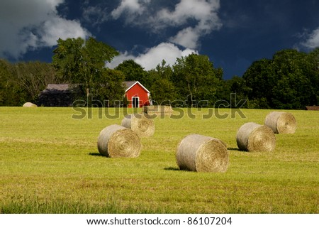 round bales on a rural field with a red shed in the background - stock photo