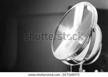 Round bathroom mirror with illumination, black and white monochrome photo - stock photo