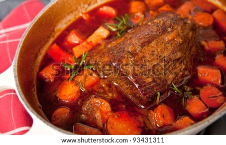 Round Beef Roast Prepared with Carrots and Yams in French Oven - stock photo