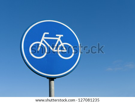 round bicycle lane sign against a blue sky - stock photo