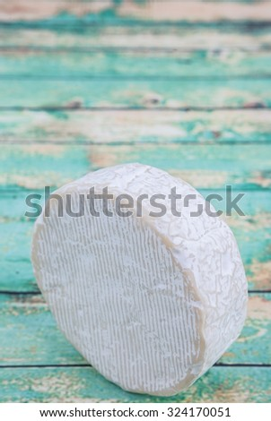 Round blue cheese over wooden background