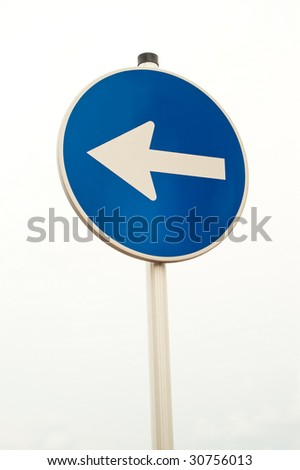 Round blue sign with arrow isolated against white sky