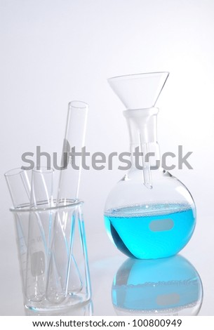 Round-bottom flask and glass funnel on white blackground isolation for use in chemcial science laboratory. Blue soltion inside it.