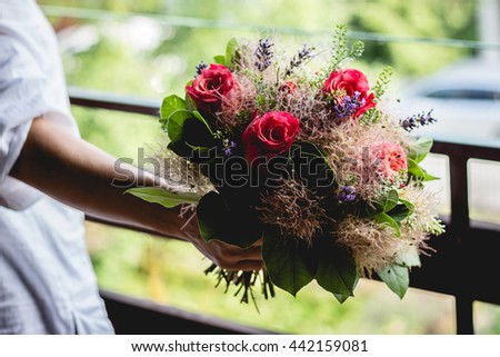 round bouquet of red roses in a girls hand