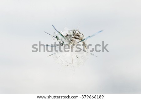 Round bullet hole in the glass with radial cracks - stock photo