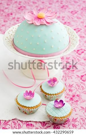Round cake and three cupcakes decorated with fondant and gum paste flowers