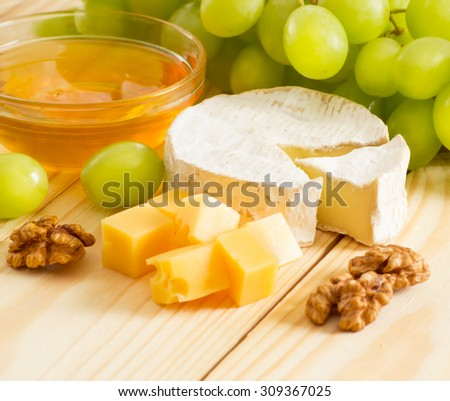 Round camembert and smoked cheese, honey, walnuts and grapes on the wooden board