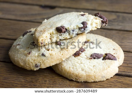 Round chocolate chip shortbread biscuits. On rustic wood.