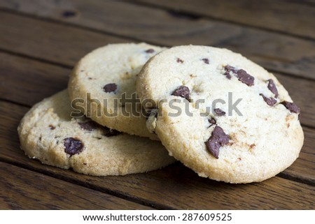 Round chocolate chip shortbread biscuits. On rustic wood. - stock photo