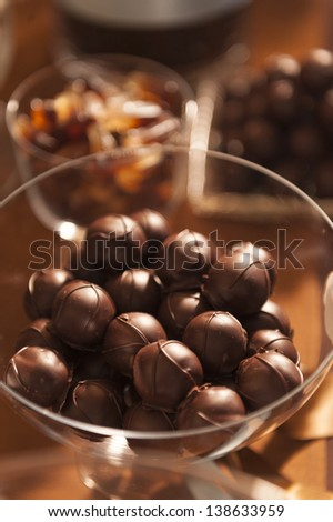 Round chocolate covered candies in a glass bowl. - stock photo