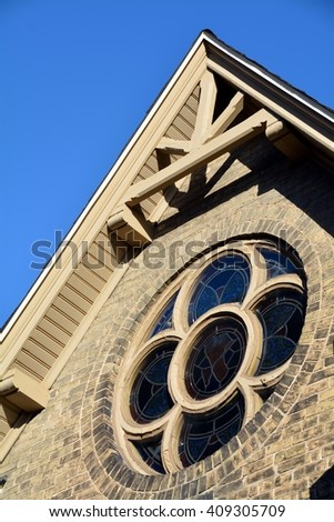 Round church window with gabled roof - stock photo