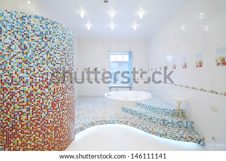 Round clean jacuzzi and stairs in spacious white bathroom with tiles with poppies. - stock photo