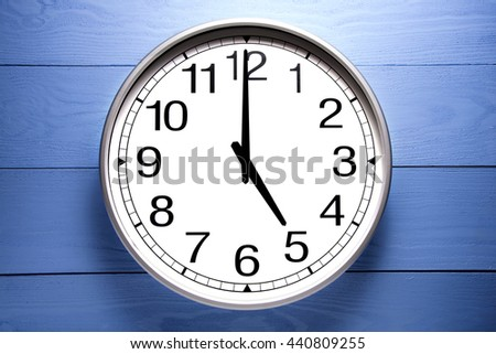 Round clock shows shows at 5 o'clock, clock on blue background - stock photo