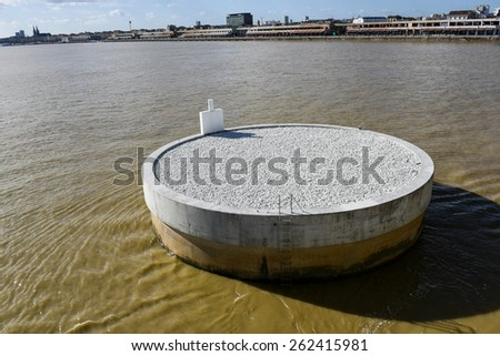 round concrete structure in the middle of the river Garonne with the view of Bordeaux City (France)  - stock photo