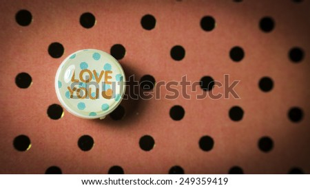 Round cute thumbtack or pushpin for whiteboard, notice board, gift card or special occasions with Love You message on polka dot vintage patterns background. Slightly defocused and close-up shot - stock photo