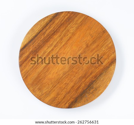 Round cutting board from dark wood - stock photo