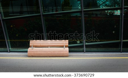 Round designed wooden bench with glassed building in background - stock photo