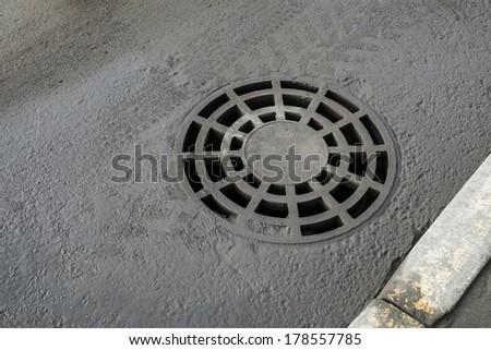 Round drainage sewer manhole cover on urban asphalt road - stock photo