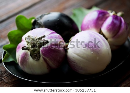 Round eggplants on an old metal tray - stock photo