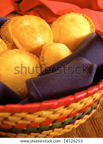 Round empanadas from mexico, in a basket on a table. - stock photo