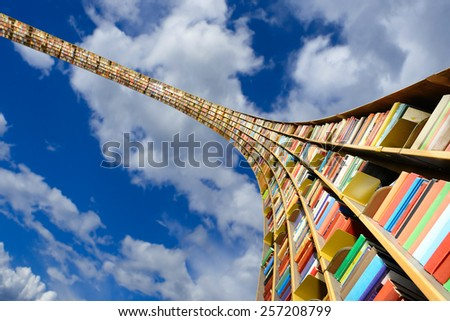 Round flying bookshelf against blue sky - stock photo