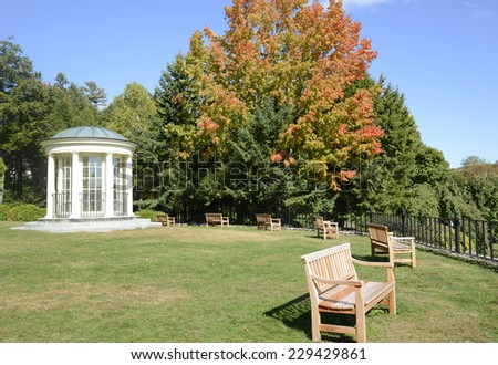 round gazebo and wood park benches by a black iron fence.  There is a grass area and trees, with leaves starting to change colors - stock photo