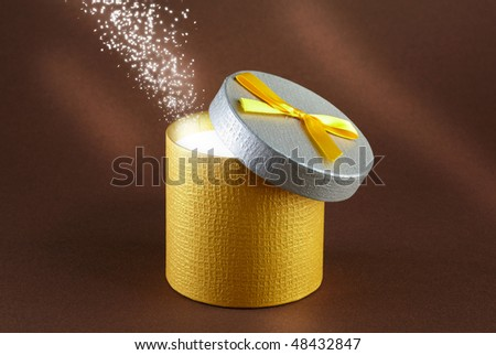 round gift box with yelow ribbon and light interior - stock photo